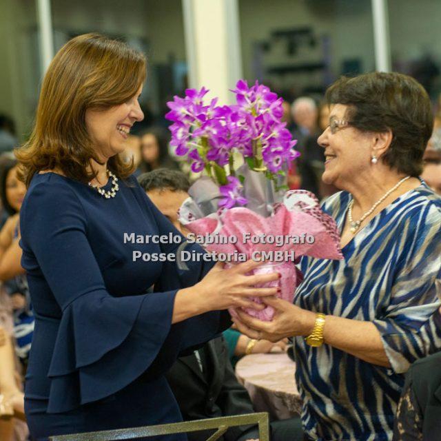 Helga Maria Camelier Guimarães, esposa do Cel Ney, entregando um arranjo de flores a Ione Diniz Martins, esposa do Ten Cel Dias